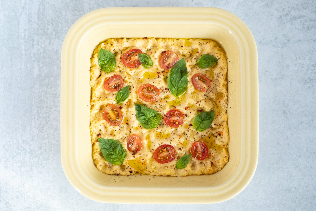 focaccia ready to go into the oven topped with tomatoes, basil and spices