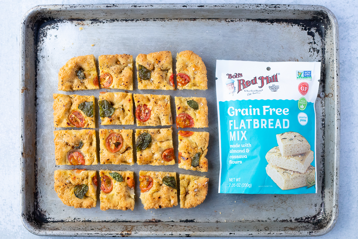 baking sheet with squares of cooked focaccia and a bag of bob's red mill focaccia mix