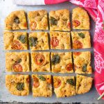 close up of grain free focaccia squares topped with basil, spices, and tomatoes