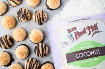 mini macaroons on a baking sheet with shredded coconut