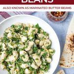 white bowl of marinated gigantes beans and fresh herbs with pita brad