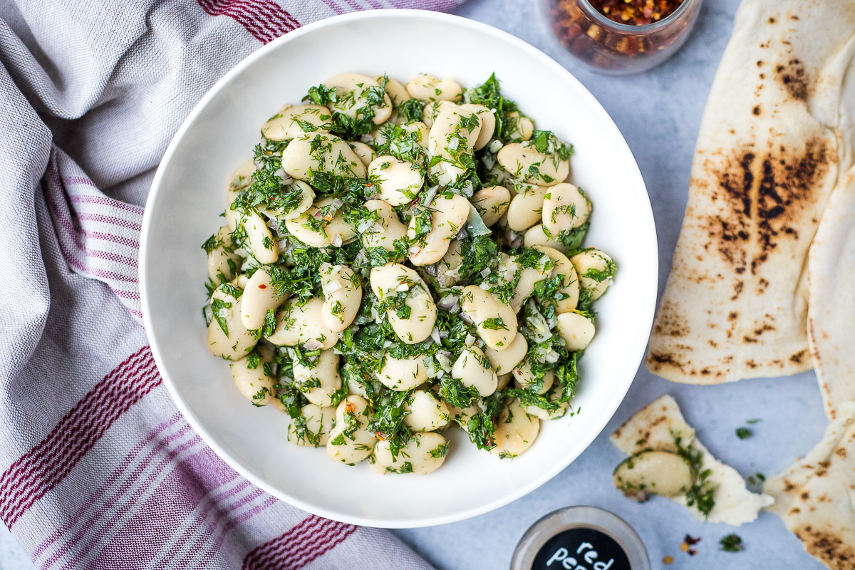 white bowl of marinated gigantes beans with pita bread on the side
