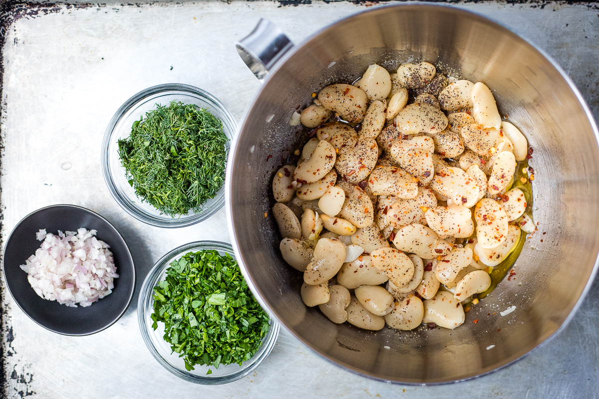 cooked butter beans in a bowl with small bowls of chopped herbs and shallots