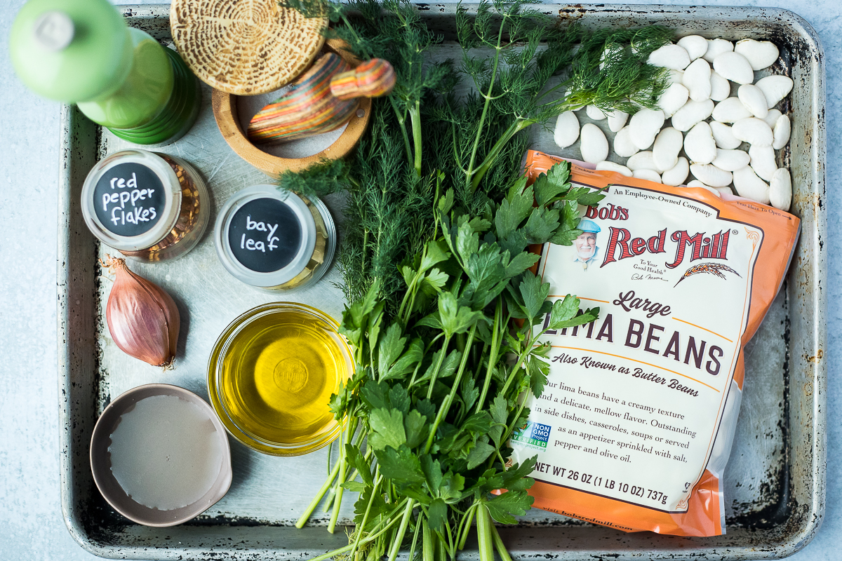 ingredients for marinated gigantes beans on a baking sheet