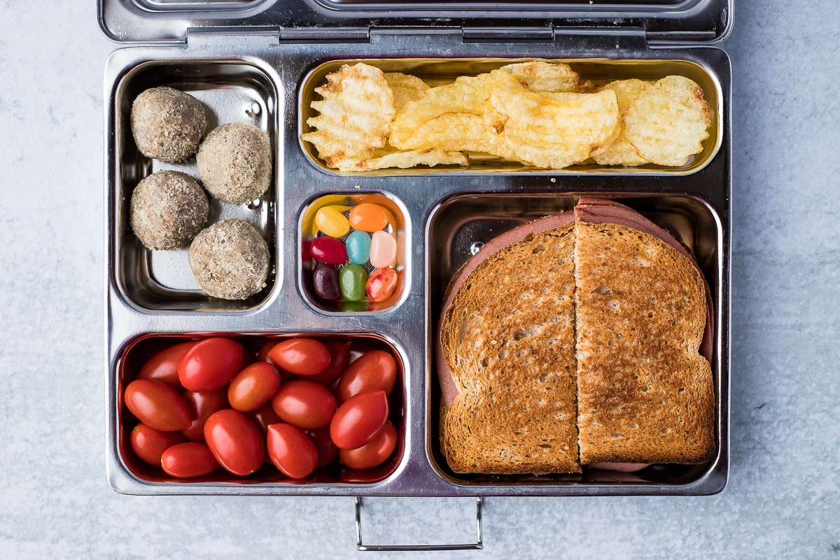 packed lunchbox including a sandwich, potato chips, tomatoes, jelly beans and energy balls