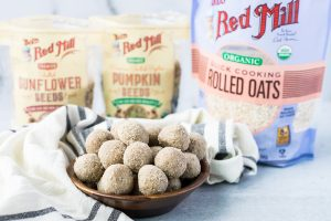 small wood bowl of energy balls with opened bags of oats, sunflower seeds and pumpkin seeds in the background