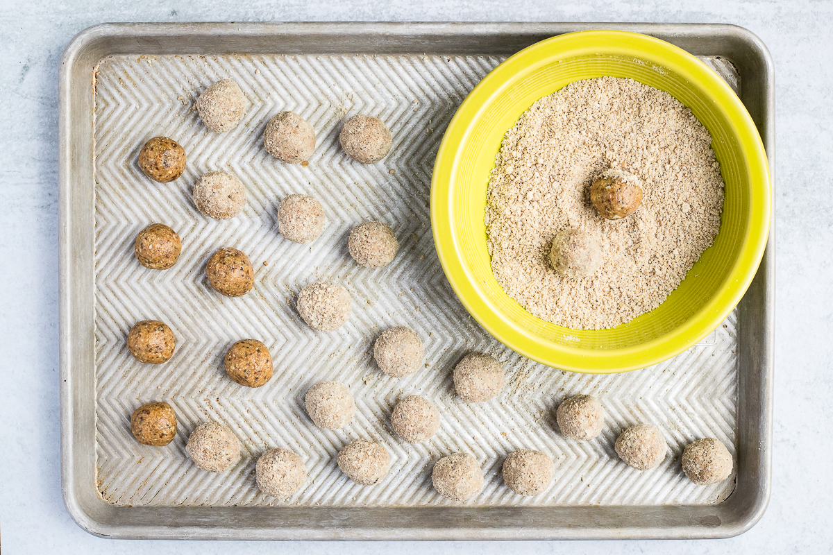 baking sheet with energy balls and green bowl with flour for rolling