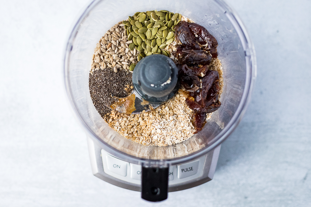overhead of food processor filled with ingredients to make nut free energy balls